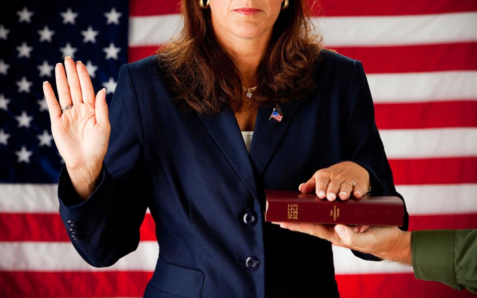 image-of-Woman-Taking-an-Oath-on-the-Bible-in-front-a-US-flag-backdrop